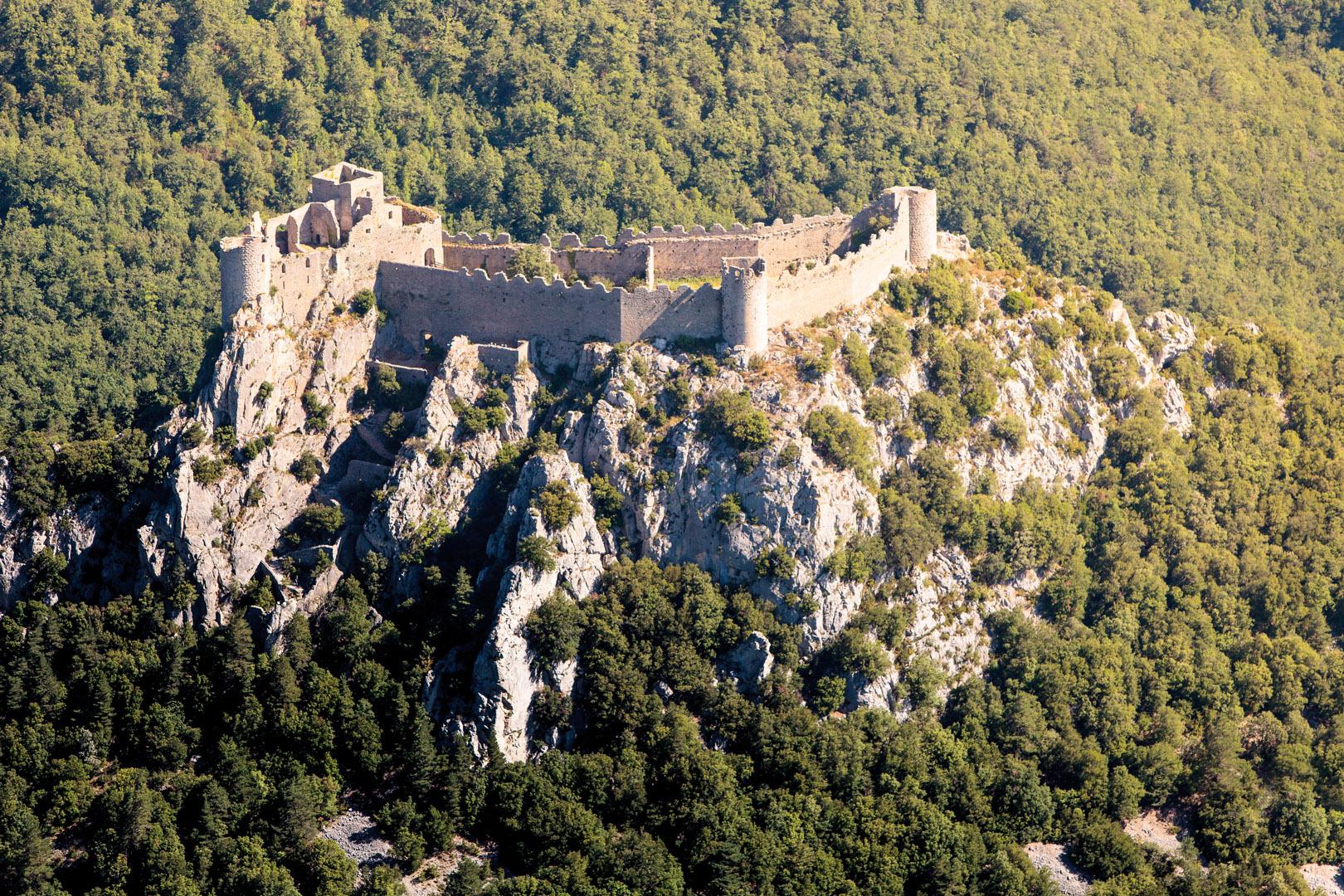 Le château de Puilaurens : son imposante silhouette crénelée a ainsi gardé toute sa hauteur, surgissant à 697m d'altitude au sommet d'une crête abrupte, au-dessus des forêts ondulantes de la vallée de la Boulzane.