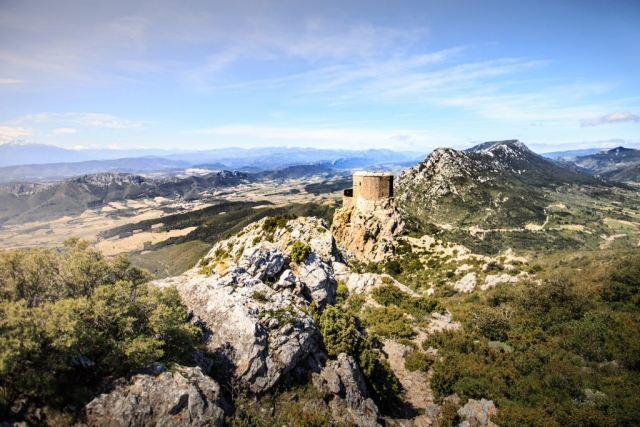 La position stratégique du château de Quéribus, aux confins des anciens royaumes de France et d'Aragon, qui lui a valu d'être promu forteresse royale par Saint-Louis au XIIIe siècle.